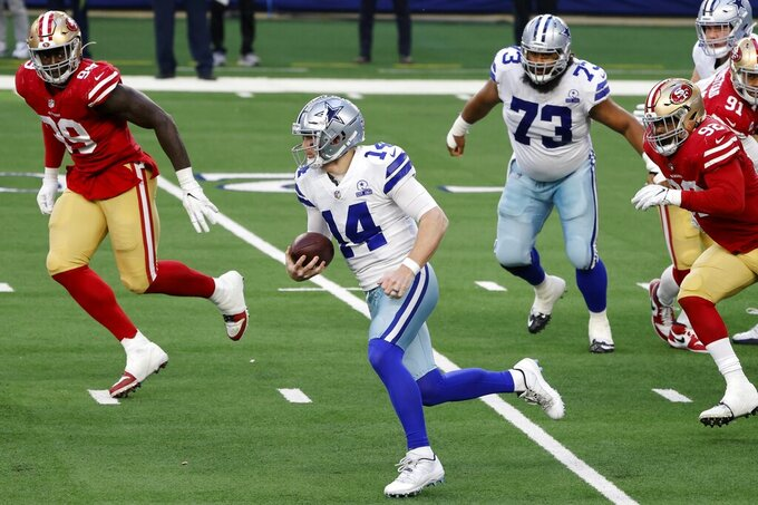 Dallas Cowboys quarterback Andy Dalton (14) keeps the ball for a gain of yardage as San Francisco 49ers defensive tackle Javon Kinlaw (99) and Kerry Hyder Jr. (92) give chase in the second half of an NFL football game in Arlington, Texas, Sunday, Dec. 20, 2020. (AP Photo/Michael Ainsworth)