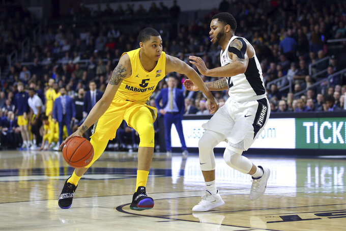 Marquette's Greg Elliott (5) is defended by Providence's Luwane Pipkins (12) during the first half of an NCAA college basketball game Saturday, Feb. 22, 2020, in Providence, R.I. (AP Photo/Stew Milne)