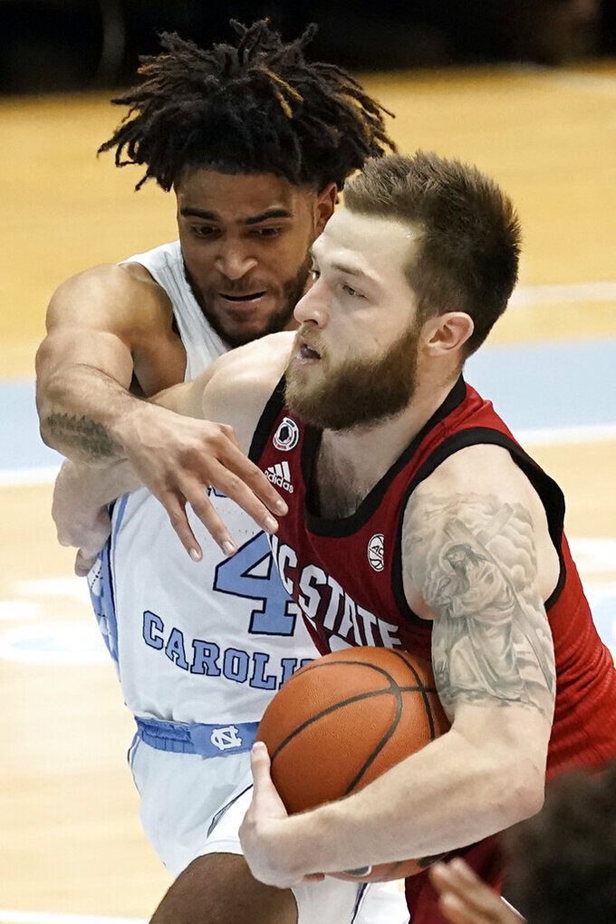 North Carolina guard R.J. Davis (4) guards North Carolina State guard Braxton Beverly during the second half of an NCAA college basketball game in Chapel Hill, N.C., Saturday, Jan. 23, 2021. (AP Photo/Gerry Broome)