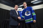 Vancouver Canucks defenseman Tyler Myers, right, and General Manager Jim Benning shake hands while posing for photos before a news conference after Myers signed a five-year contract with the NHL hockey team, in Vancouver, British Columbia, Monday, July 1, 2019. (Darryl Dyck/The Canadian Press via AP)