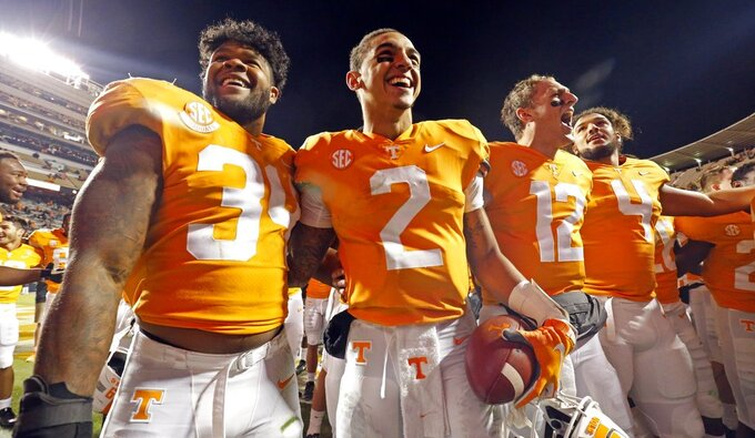 FILE - In this Nov. 10, 2018, file photo, Tennessee quarterback Jarrett Guarantano (2) celebrates with teammates linebacker Darrin Kirkland Jr. (34), quarterback JT Shrout (12), and tight end Dominick Wood-Anderson (4) after an NCAA college football game against Kentucky in Knoxville, Tenn. Tennessee won 24-7. Tennessee has an opportunity Saturday to show how far it has come in the last year. The Volunteers can become bowl eligible by beating Missouri in their home finale. (AP Photo/Wade Payne, File)