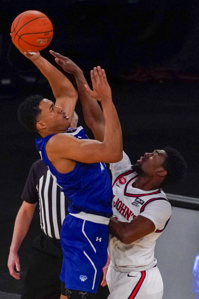 Seton Hall guard Jared Rhoden, left, goes to the basket against St. John's guard Greg Williams Jr. during overtime of an NCAA college basketball game in the quarterfinals of the Big East conference tournament, Thursday, March 11, 2021, in New York. Seton Hall won 77-69. (AP Photo/Mary Altaffer)
