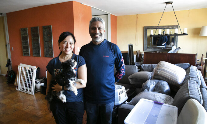 Joyce and Anil Lilly pose in their living room with their dog Max as they move out of their Bronx apartment, Tuesday, July 21, 2020, in New York. If the outbreak roars back in the city, they will not be sheltering again in the apartment. They just bought a house an hour north in the Hudson Valley. (AP Photo/Mark Lennihan)