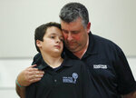 Tony Montalto hugs his son Anthony as they attend a news conference by Florida governor Ron DeSantis, Wednesday, Feb. 13, 2019, in Fort Lauderdale, Fla. DeSantis ordered a statewide grand jury investigation on school safety. Montalto is the father of Gina Montalto, who was killed during the Parkland school shooting. (AP Photo/Wilfredo Lee)