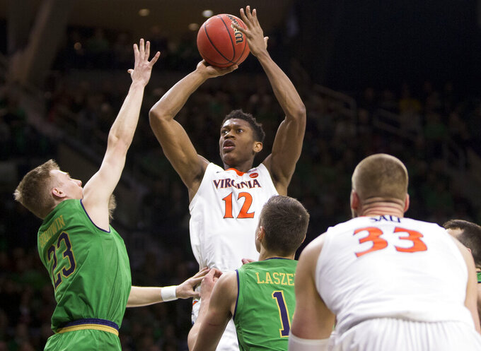Virginia's De'Andre Hunter (12) goes up for a shot over Notre Dame's Dane Goodwin (23) and Nate Laszewski during the first half of an NCAA college basketball game Saturday, Jan. 26, 2019, in South Bend, Ind. (AP Photo/Robert Franklin)