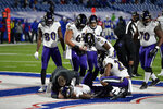 A trainer checks on Baltimore Ravens quarterback Lamar Jackson, below, after he was injured during the second half of an NFL divisional round football game against the Buffalo Bills Saturday, Jan. 16, 2021, in Orchard Park, N.Y. (AP Photo/Adrian Kraus)