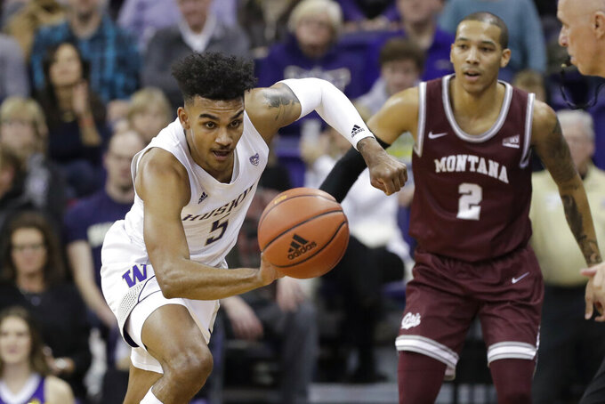 Washington's Jamal Bey (5) chases down a loose ball in front of Montana's Kendal Manuel (2) during the second half of an NCAA college basketball game Friday, Nov. 22, 2019, in Seattle. (AP Photo/Elaine Thompson)