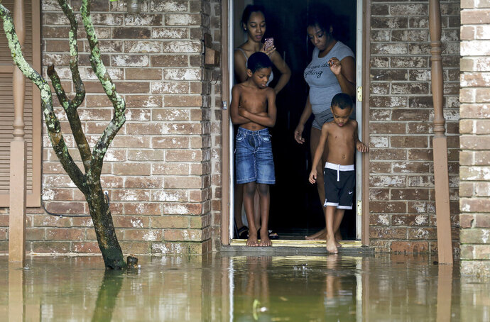 Eight-year-old Cam'ron Maltie, left, and Adrian Murray, 4, look at the their flooded front lawn during Tropical Storm Beta, Tuesday, Sept. 22, 2020, in Houston. Their family has been living in the home for a year and didn't know the neighborhood flooded. (Godofredo A. Vásquez/Houston Chronicle via AP)