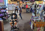 People wear face masks to protect against the spread of the coronavirus at a night market in Taipei, Taiwan, Friday, May 14, 2021. (AP Photo/Chiang Ying-ying)