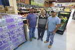 Singh Maan, center, poses for a photo with his sons CJ Maan, left, and Ricky Maan, right, Monday, Sept. 27, 2021, in the grocery store they own in Chester, Mont., near the scene where an Amtrak train derailed Saturday, killing three people and injuring others. When the crash happened, the family rushed to the scene with first-aid and food supplies taken right from the shelves of their store. (AP Photo/Ted S. Warren)