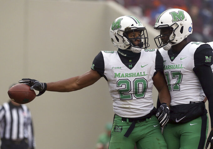 Brenden Knox (20) of Marshall celebrates a touchdown run with quarterback Isaiah Green (17) in the first half  of an NCAA college football game in Blacksburg Va. Saturday, Dec. 1 2018. (Matt Gentry/The Roanoke Times via AP)