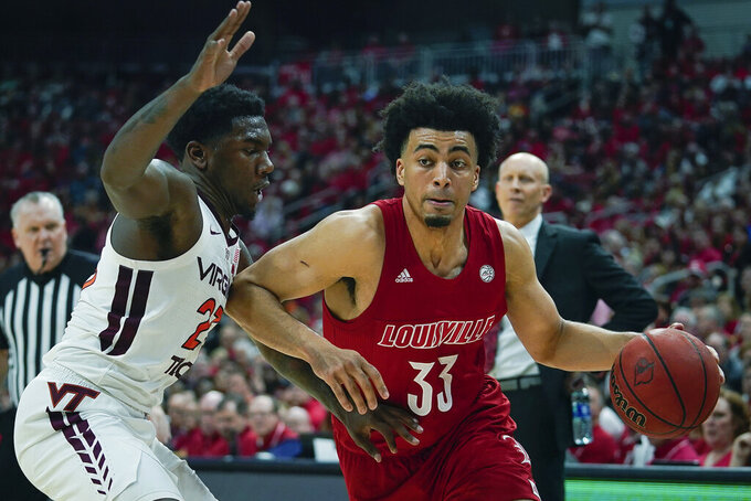 Louisville forward Jordan Nwora (33) dribbles past Virginia Tech guard Tyrece Radford (23) during the second half of an NCAA college basketball game, Sunday, March 1, 2020 in Louisville, Ky. (AP Photo/Bryan Woolston)