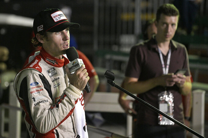 Ryan Blaney answers questions from reporters in Victory Lane after winning a NASCAR Cup Series auto race at Daytona International Speedway, Saturday, Aug. 28, 2021, in Daytona Beach, Fla. (AP Photo/Phelan M. Ebenhack)