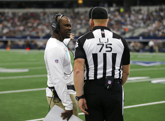 Miami Dolphins head coach Brian Flores, left, talks to side judge Rob Vernatchi (75) in the second half of an NFL football game against the Dallas Cowboys in Arlington, Texas, Sunday, Sept. 22, 2019. (AP Photo/Michael Ainsworth)