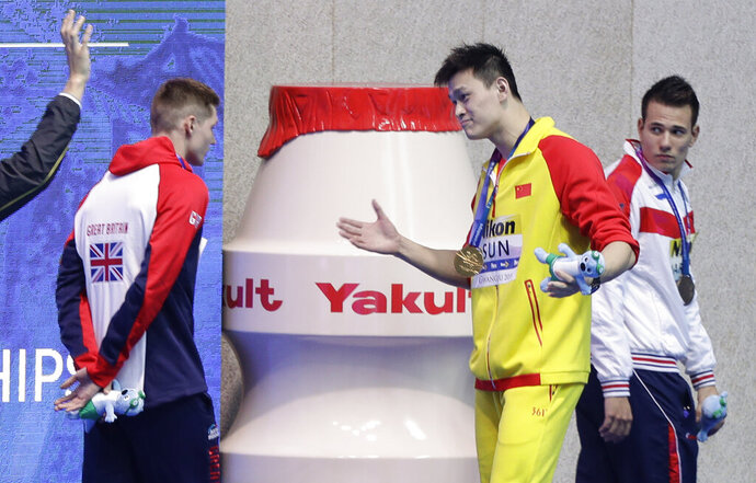 FILE - In this Tuesday, July 23, 2019 file photo, gold medalist China's Sun Yang gestures to Britain's bronze medalist Duncan Scott, left, following the medal ceremony in the men's 200m freestyle final at the World Swimming Championships in Gwangju, South Korea. One of China's biggest Olympic stars will undergo a rare public trial of a doping case on Friday, Nov. 15, 2019 with his 2020 Tokyo Games place at stake. Three-time gold medalist swimmer Sun Yang is facing a World Anti-Doping Agency appeal in Switzerland that seeks to ban him for up eight years. (AP Photo/Mark Schiefelbein, File)