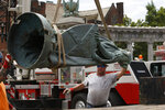 A workman guides the statue from the Jefferson Davis monument onto a flatbed truck after it was removed from its pedestal on Monument Ave. in Richmond, Va., Wednesday, July 8, 2020. The figure was atop a 65 foot tall Doric column topped by a bronze figure called