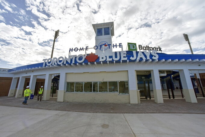 FILE - In this Sunday, Feb. 16, 2020 file photo, Construction workers walk past the main entrance to the TD Ballpark, the Florida home of Toronto Blue Jays, as they get the stadium ready in Dunedin, Fla. The Toronto Blue Jays will play their first two homestands of the regular season at their spring training facility in Dunedin, Florida, because of Canadian government restrictions during the coronavirus pandemic, a person familiar with the matter told The Associated Press. The Blue Jays planned to make the announcement on Thursday morning. Feb. 18, 2021 (Steve Nesius/The Canadian Press via AP, File)