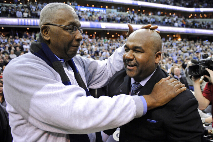 "FILE - In this March 9, 2013, file photo, former Georgetown coach John Thompson Jr., left, congratulates his son Georgetown head coach John Thompson III, right, after the Hoya's 61-39 win over Syracuse in an NCAA college basketball game in Washington. John Thompson, the imposing Hall of Famer who turned Georgetown into a ""Hoya Paranoia"" powerhouse and became the first Black coach to lead a team to the NCAA men's basketball championship, has died. He was 78 His death was announced in a family statement Monday., Aug. 31, 2020. No details were disclosed. (AP Photo/Nick Wass, File)"