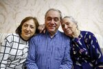 Adil Sharifov poses for a photo with his sister Kamala Sharifova and his mother Adila Ahmadova at home in Baku, Azerbaijan, Friday, Nov. 20, 2020. Adil Sharifov, 62, who left his hometown in 1992 during the first war and lives in Azerbaijan's capital, Baku, knows he will find similar devastation if he returns to the city of Jabrayil, which he longs to do. (AP Photo/Aziz Karimov)