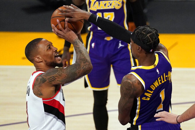 Los Angeles Lakers guard Kentavious Caldwell-Pope (1) blocks a shot by Portland Trail Blazers guard Damian Lillard (0) during the first half of an NBA basketball game Friday, Feb. 26, 2021, in Los Angeles. (AP Photo/Mark J. Terrill)