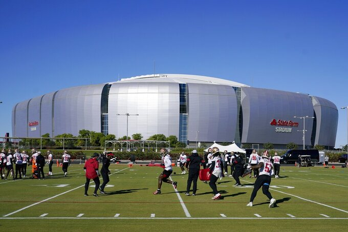 The San Francisco 49ers NFL football team defensive unit runs drills during practice in front of State Farm Stadium, home of the Arizona Cardinals, Thursday, Dec. 3, 2020, in Glendale, Ariz. The 49ers start a three-week road trip after being forced from their stadium and practice facility because of strict new COVID-19 protocols in their home county in Northern California. (AP Photo/Ross D. Franklin)