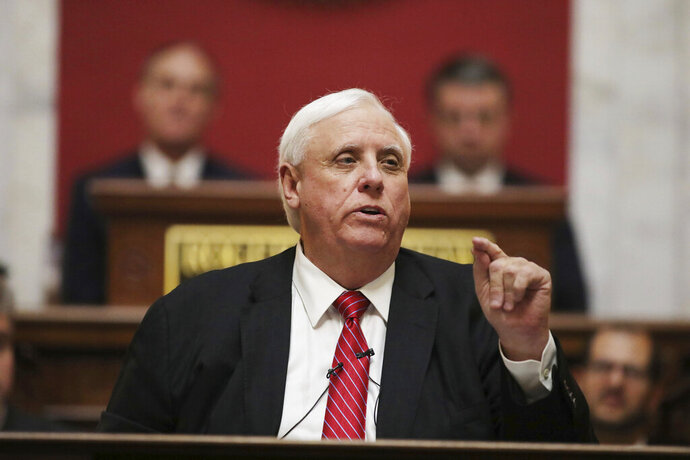FILE - In this Jan. 8, 2020, file photo, West Virginia Governor Jim Justice delivers his annual State of the State address in the House Chambers at the state capitol, in Charleston, W.Va. Gov. Justice has tightened restrictions on three counties and ordered in the National Guard to try and curb a coronavirus hotspot in the state's eastern panhandle, which includes suburbs of Washington. In an executive order Friday, April 3, 2020, the Republican restricted people in Berkeley, Jefferson and Morgan counties to gatherings of no more five. (AP Photo/Chris Jackson, File)