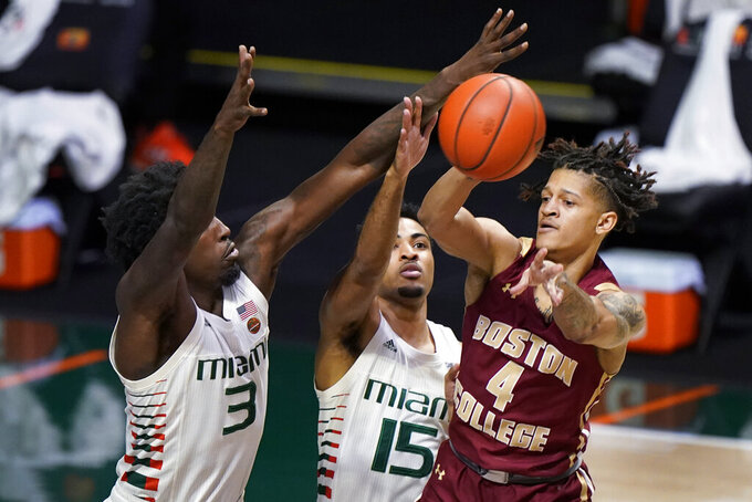 Boston College guard Makai Ashton-Langford (4) passes the ball past Miami center Nysier Brooks (3) and guard Willie Herenton (15) during the first half of an NCAA college basketball game, Friday, March 5, 2021, in Coral Gables, Fla. (AP Photo/Wilfredo Lee)