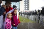 FILE - In this Sunday, Sept. 6, 2020 file photo, people with their children stand at a barbed wire fence in front of a police line toward the Independence Palace, residence of the President Alexander Lukashenko, during Belarusian opposition supporters rally in Minsk, Belarus. Belarus President Alexander Lukashenko has relied on massive arrests and intimidation tactics to hold on to power despite nearly three months of protests sparked by his re-election to a sixth term, but continuing protests have cast an unprecedented challenge to his 26-year rule. (AP Photo/TUT.by, File)