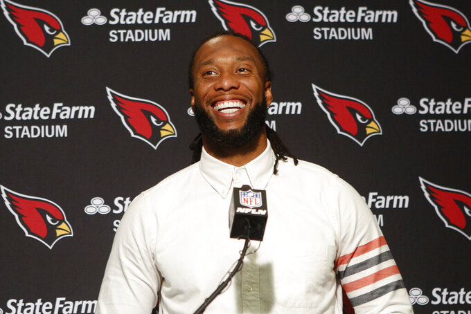 FILE - In this Oct. 6, 2019, file photo, Arizona Cardinals wide receiver Larry Fitzgerald attends a news conference after winning an NFL football game against the Cincinnati Bengals, in Cincinnati. Fitzgerald is coming back to the team for the 2020 season. There was speculations the 36-year-old Fitzgerald might retire, but the team announced Wednesday, Jan. 15, 2020, he has signed a one-year contract. (AP Photo/Frank Victores, File)