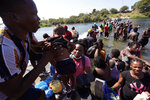 Haitian migrants use a dam to cross to and from the United States from Mexico, Friday, Sept. 17, 2021, in Del Rio, Texas. Thousands of Haitian migrants have assembled under and around a bridge in Del Rio presenting the Biden administration with a fresh and immediate challenge as it tries to manage large numbers of asylum-seekers who have been reaching U.S. soil. (AP Photo/Eric Gay)