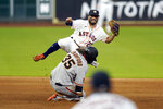 Houston Astros second baseman Jose Altuve (27) tries to turn a double play as he avoids San Francisco Giants' Brandon Crawford (35) during the fifth inning of a baseball game Tuesday, Aug. 11, 2020, in Houston. Crawford was out at second and the Giants' Chadwick Tromp was safe at first. (AP Photo/David J. Phillip)