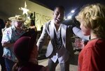 Leslie Odom Jr., the actor that plays the role of Aaron Burr greets people at the entrance plaza of the Santurce Fine Arts Center moments before the premiere of the award-winning Broadway musical, Hamilton, starring its creator, New York native of Puerto Rican descent Lin-Manuel Miranda, in San Juan, Puerto Rico, Friday Jan. 11, 2019. The musical is set to run for two weeks and will raise money for local arts programs. (AP Photo/Carlos Giusti)