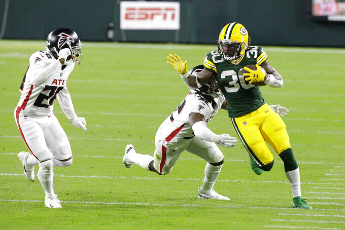 Green Bay Packers' Jamaal Williams (30) is tackled by Atlanta Falcons' Jaylinn Hawkins (32) and Kendall Sheffield (20) nduring the first half of an NFL football game, Monday, Oct. 5, 2020, in Green Bay, Wis. (AP Photo/Mike Roemer)