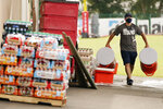 A Tennessee Titans staff member removes drink containers from the practice fields after practice was called off during NFL football training camp Thursday, Aug. 27, 2020, in Nashville, Tenn. (AP Photo/Mark Humphrey, Pool)