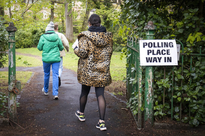 People arrive to vote at a polling station in Glasgow, Scotland, Thursday May 6, 2021. Scots are heading to the polls to elect the next Scottish Government - though the coronavirus pandemic means it could be more than 48 hours before all the results are counted. (Jane Barlow/PA via AP)