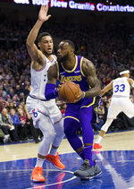 Los Angeles Lakers' LeBron James, right, makes his move against Philadelphia 76ers' Ben Simmons, left, of Australia, during the first half of an NBA basketball game, Sunday, Feb. 10, 2019, in Philadelphia. (AP Photo/Chris Szagola)