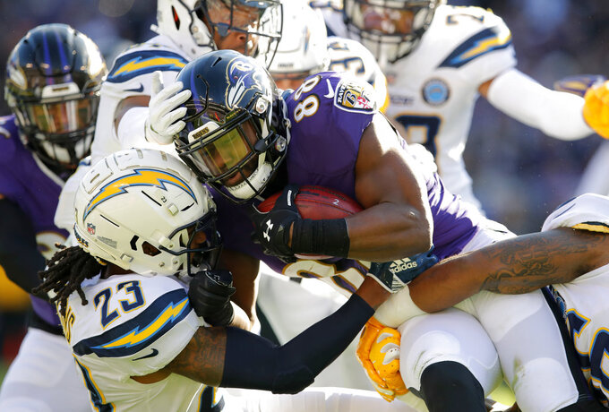 Baltimore Ravens running back Ty Montgomery (88) is tackled by Los Angeles Chargers defensive back Rayshawn Jenkins (23) as he rushes the ball in the first half of an NFL wild card playoff football game, Sunday, Jan. 6, 2019, in Baltimore. (AP Photo/Carolyn Kaster)