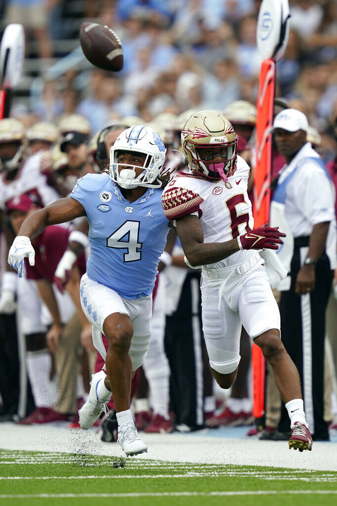 North Carolina defensive back Trey Morrison (4) and Florida State wide receiver Keyshawn Helton (6) chase a pass during the first half of an NCAA college football game in Chapel Hill, N.C., Saturday, Oct. 9, 2021. The pass fell incomplete. (AP Photo/Gerry Broome)
