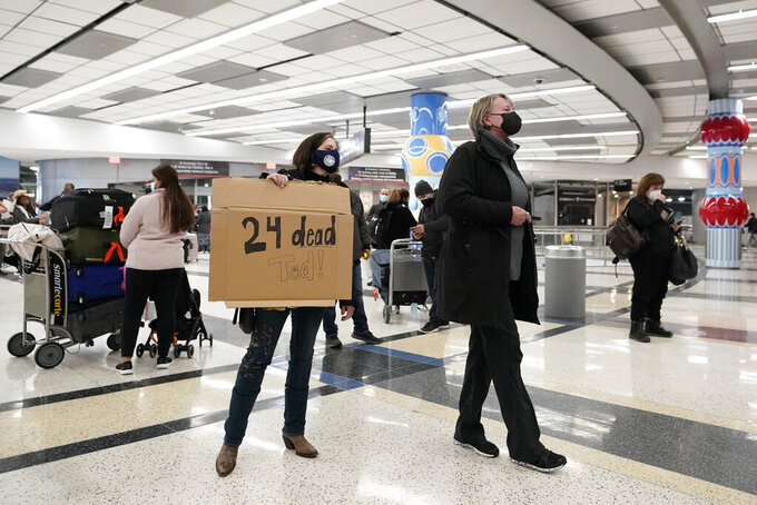 Mary Kay Hoffman, left, and Cindy Durham, right, wait for the arrival of Sen. Ted Cruz, R-Texas, at the international arrivals terminal at George Bush Intercontinental Airport Thursday, Feb. 18, 2021, in Houston. Sen. Cruz has acknowledged that he traveled to Mexico for a family vacation this week as his home state was paralyzed by a deadly winter storm. In a statement Thursday, Cruz said he was returning to Texas.  (AP Photo/David J. Phillip)