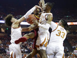 Iowa State guard Talen Horton-Tucker, second from left, is fouled as he drives to the basket against Texas defenders Jaxson Hayes, left, Jase Febres (13) and Kamaka Hepa (33) during the first half of an NCAA college basketball game, Saturday, March 2, 2019, in Austin, Texas. (AP Photo/Eric Gay)