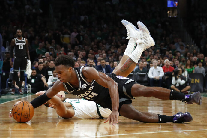 Sacramento Kings' Buddy Hield, foreground, dives for the ball in front of fallen Boston Celtics' Carsen Edwards during the fourth quarter of an NBA basketball game Monday, Nov. 25, 2019, in Boston. (AP Photo/Winslow Townson)