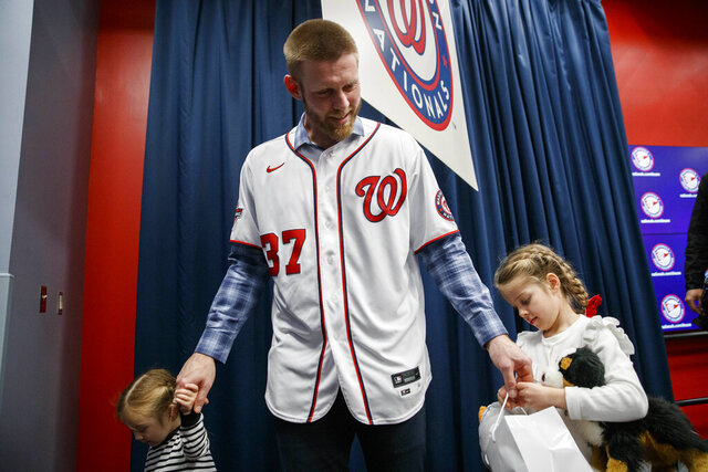 Washington Nationals pitcher Stephen Strasburg, center, departs with his daughters after a baseball media availability at Nationals Park, Tuesday, Dec. 17, 2019, in Washington. (AP Photo/Alex Brandon)