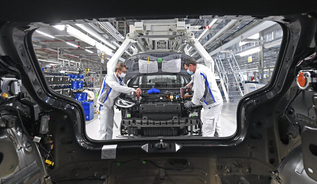 Max Bruehmann (l) and Heiko Gruner employees of German car producer Volkswagen Sachsen, work with face masks in the assembly of the ID.3 in the vehicle plant in Zwickau, Germany, Thursday, April 23, 2020. At carmaker Volkswagen, vehicle production restarts after a corona shutdown of more than five weeks. Production of the all-electric ID.3 will initially be restarted with reduced capacity and cycle time. Zwickau is the first VW vehicle plant in Germany to resume operations. (Hendrik Schmidt/dpa via AP)