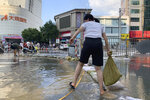 A woman moves a sandbag along a flooded road in the aftermath of the heaviest recorded rainfall in Zhengzhou in central China's Henan province on Saturday, July 24, 2021. Rescuers used bulldozers and rubber boats to move residents out of flooded neighborhoods in central China on Saturday after torrential rains killed at least 56 people. (AP Photo/Dake Kang)