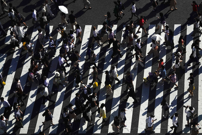 Pedestrians cast shadows as they walk across the famous Shibuya crossing Thursday, June 13, 2019, in Tokyo. It's not just a crossing. Located just outside Shibuya Station, the scramble crossing is one of the top tourist attractions in Japan. It's so famous that there's an observation deck on the rooftop of a building built to watch the crossing. During rush hour, an estimated 1000 to 2500 people cross the intersection during each traffic light change. (AP Photo/Jae C. Hong)
