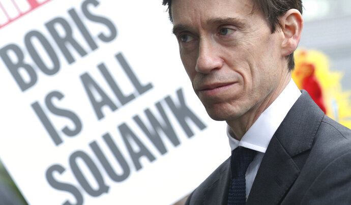 A poster is brandished during a public demonstration as Conservative party leadership contender Rory Stewart arrives at the television studios ahead of a scheduled live television debate for the Conservative Party leadership candidates, in London, Sunday June 16, 2019.  Five out of the six candidates will appear in the first TV debate, with Boris Johnson declining to take part, although other candidates accuse him of trying to avoid scrutiny. (Yui Mok/PA via AP)
