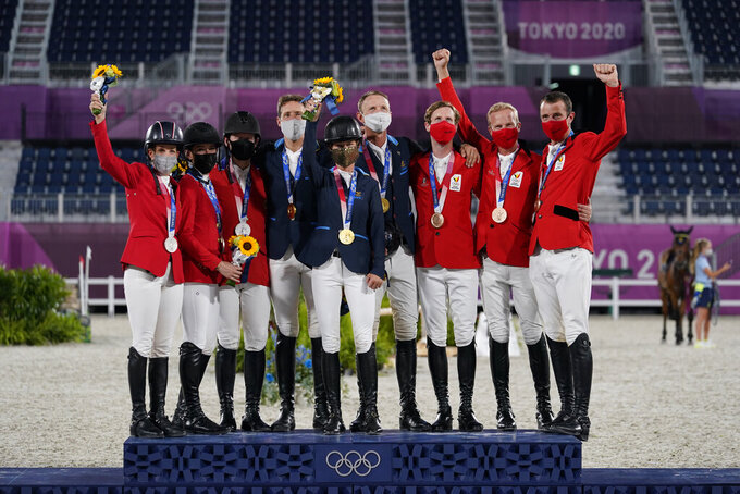 From left, silver medal winners United States' team of Laura Kraut, Jessica Springsteen and McLain Ward, gold medal winners Sweden's team of Henrik von Eckermann, Malin Baryard-Johnsson and Peder Fredricson, and bronze medal winners Belgium's Pieter Devos, Jerome Guery and Gregory Wathelet gather during a equestrian jumping team medal ceremony at the 2020 Summer Olympics, Saturday, Aug. 7, 2021, in Tokyo, Japan. (AP Photo/Carolyn Kaster)