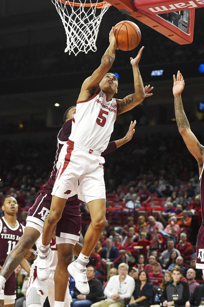 Arkansas guard Jalen Harris (5) shoots in front of Texas A&M defender Savion Flagg (1) during the first half an NCAA college basketball game, Saturday, Feb. 23, 2019, in Fayetteville, Ark. (AP Photo/Michael Woods)