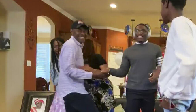 In this still image from video provided by the NFL, Jeff Okudah, second from right, celebrates during the NFL football draft Thursday, April 23, 2020. (NFL via AP)