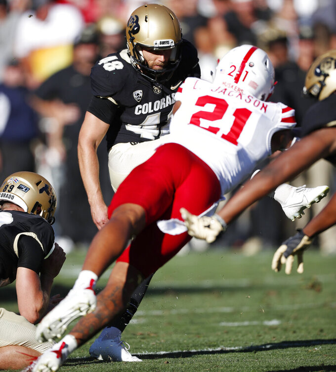 Colorado place kicker James Stefanou, back, kicks the go-ahead field goal as Nebraska cornerback Lamar Jackson dives to block the kick in overtime of an NCAA college football game Saturday, Sept. 7, 2019, in Boulder, Colo. Colorado won 34-31 in overtime. (AP Photo/David Zalubowski)